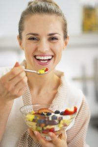 gülen genç kız meyve salatası yiyor